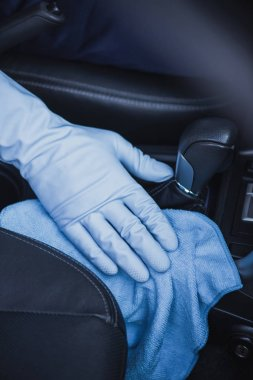 cropped view of car cleaner wiping gear shifter with rag