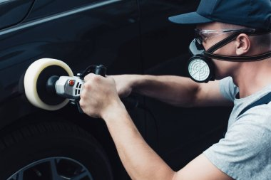 car cleaner in respirator and protective glasses polishing car with buffer machine