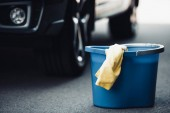Photo blue bucket and yellow rag on asphalt near black car