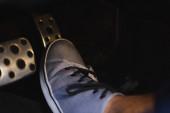 Teilansicht des männlichen Beines in Turnschuhen am Bremspedal