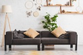 belső tér hangulatos nappali kanapéval, növényi és álomfogók téglafalon