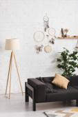 interiér útulného obývacího pokoje s pohovkou, lampou a lapači snů na bílé stěně