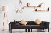 interiér útulného obývacího pokoje s pohovkou, lampou a lapači snů na stěně