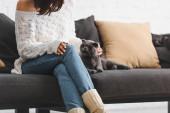 abgeschnittene Ansicht der schönen Frau in Decke, die auf dem Sofa mit Katze sitzt