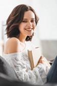 gyönyörű mosolygós lány olvasás könyvet kanapén otthon