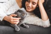 fröhliche Frau liegt mit schottischer Faltkatze auf Sofa