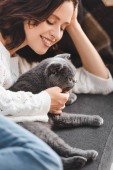 Fotografie beautiful happy girl lying on sofa with scottish fold cat