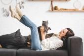 Photo beautiful cheerful girl lying on sofa with scottish fold cat