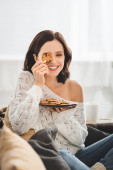 Photo beautiful smiling girl sitting on sofa with cookies
