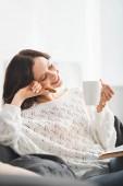 šťastná žena sedí na pohovce se sušenkou, šálkem kávy a knihou