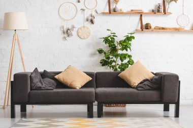 interior of cozy living room with sofa, plant and dream catchers on brick wall