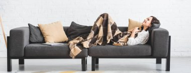 Happy brunette girl in blanket lying on sofa with laptop stock vector