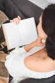 kivágott kilátás fiatal nő takaró olvasás könyv kanapén otthon