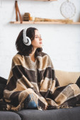 beautiful girl thinking and listening music with headphones while sitting in blanket