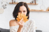 beautiful woman holding yellow autumn leaves in front of face