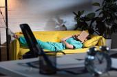 selektivní zaměření zdravotní sestry v uniformě ležící na pohovce s knihou na obličeji během noční směny