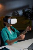 sestra v uniformě sedí u stolu s virtuální realitou sluchátka během noční směny