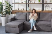 Photo pretty girl using smartphone while sitting on sofa in living room