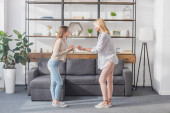 Photo side view of mother and daughter quarreling while standing in living room
