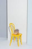 žlutá židle s knihami na bílé a šedé