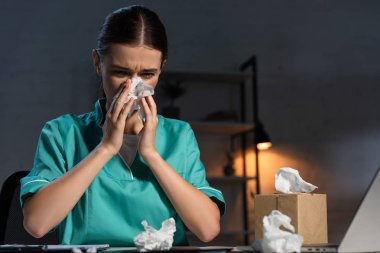 attractive nurse in uniform sneezing and holding napkin during night shift