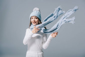 stylish smiling girl posing in knitted hat and scarf, isolated on grey