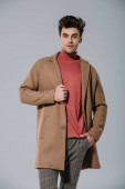 fashionable handsome man posing in beige coat, isolated on grey