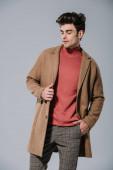 módní muž pózující v béžovém podzimním kabátě, izolovaný na šedi