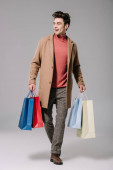 happy fashionable man in beige coat walking with shopping bags on grey