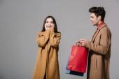 meglepett barátnő és barátja bevásárló táskák elszigetelt szürke