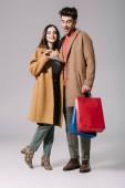 šťastný pár v béžových kabátech pózuje s nákupními taškami a kreditní kartou na šedé