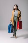 módní elegantní žena v béžovém kabátu drží nákupní tašky na šedé
