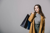 Fotografie fashionable lady in beige coat holding shopping bags, isolated on grey