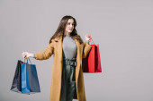 fashionable model in beige coat holding shopping bags, isolated on grey