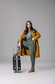Fotografie beautiful elegant woman in beige coat posing with travel bag on grey
