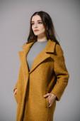 Fotografie elegant pretty woman posing in beige coat, isolated on grey