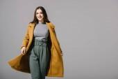 elegantní veselá dívka pózující v béžovém kabátě, izolovaná na šedé