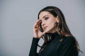 vonzó gondolkodó nő pózol fekete pulóver, elszigetelt szürke