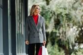 atraktivní obchodnice v kabátě a brýlích držící nákupní tašky