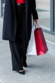 oříznutý pohled na obchodnici kráčející a držící nákupní tašky