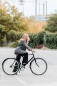 boční pohled na atraktivní podnikatelku v kabátě a brýle na kole