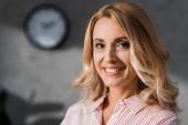 atraktivní podnikatelka v růžové košili s úsměvem a při pohledu do kamery