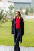 attraktive und blonde Geschäftsfrau im schwarzen Mantel, die wegschaut