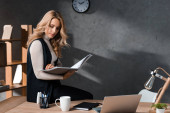 attraktive und blonde Geschäftsfrau, die Papiere hält und im Büro auf dem Tisch sitzt
