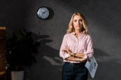 Photo attractive and blonde businesswoman in shirt holding papers in office