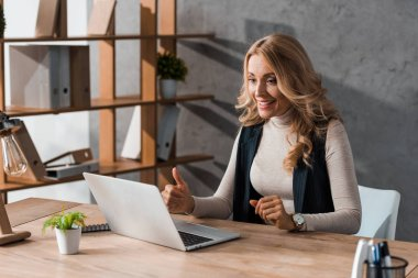 Attractive and smiling businesswoman showing thumb up and looking at laptop stock vector