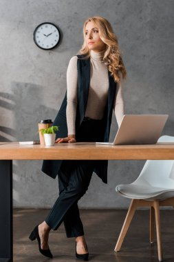 Attractive and blonde businesswoman standing and looking away in office stock vector
