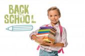 Fotografie šťastný školák drží barevné knihy v blízkosti zpět do školy dopisy na bílém