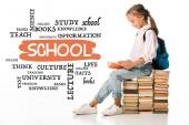 vidám iskolás gyerek ül a könyvek és az olvasás közelében betűk fehér