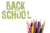 Fotografie vícebarevné tužky v blízkosti školní písmena na bílém